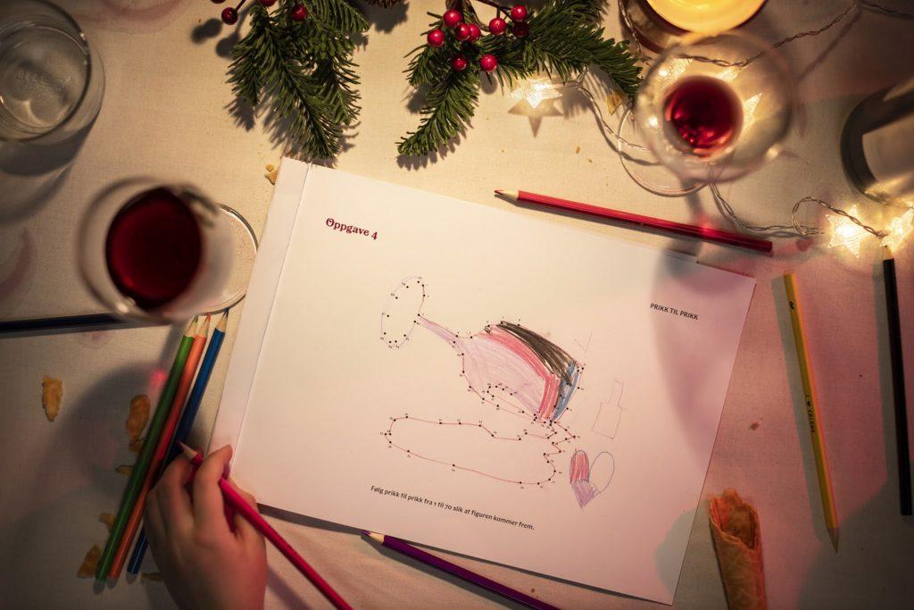 Bildet av barnehender som fargelegger et vinglass i et julehefte