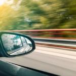 Bilde tatt ut av vinduet på en bil hvor man ser sidespeilet