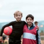 To gutter med fotball. De holder rundt hverandre og ser inn i kamera.
