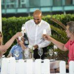 Bilde av en kelner som serverer sjampanje til et kjærestepar som skåler på en sommerdag