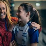 En kvinnelig trener holder rundt en jente i idrettstøy.