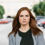Bilde av en dame som står på gata og ser inn i kamera