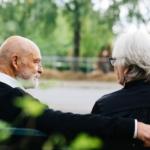 Bilde av et eldre par som sitter på en benk og snakker sammen