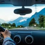 Bilde av hender som holder et bilratt i forsetet med landevei foran seg