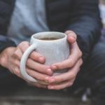 Bilde av mannshender som holder en kaffekopp