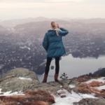 Bilde av ei dame som står på et fjell og ser ut over byen