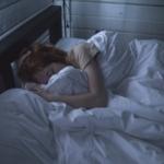 Bilde av en dame som gjemmer seg under dyna i en seng