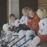 Bilde av ishockeygutter som sitter på benken og smiler si