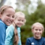 Tre jenter på fotballbanen ser inn i kamera
