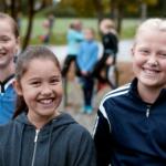 Bilde av tre jenter som smiler til kamera