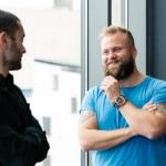 Bilde av to mannlige kolleger som smiler til hverandre under samtale