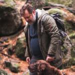 Mann på tur i skogen med hund.