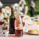 Illustrasjonsbilde med vinflasker og vinglass på et utebord om sommeren