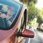 Bilde av en mannlig sjåfør som sitter bak rattet på en rød bil