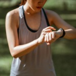 Bilde av ei ung dame som ser på pulsklokken hun har på armen under en treningsøkt.