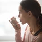 En kvinne drikker vann fra et glass.