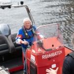 Roar, en godt voksen mann, ikledd blå jakke og redningsvest kjører en båt.