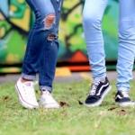 To ungdommer står foran en grafittivegg. Man ser kun bena til ungdommene.
