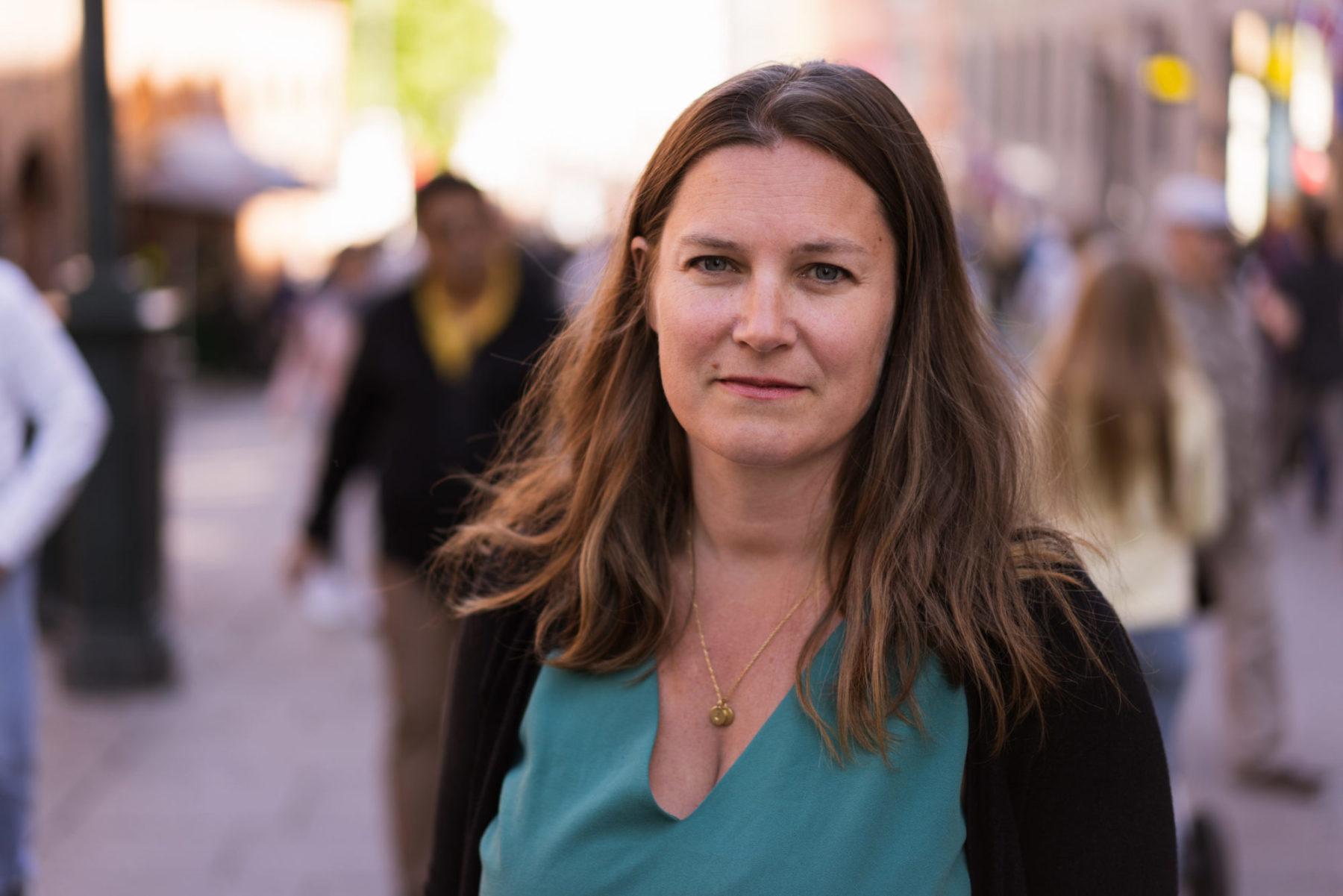 Randi Hagen Eriksrud står i en gate i byen og ser i kamera