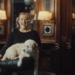 En dame i 60-årene sitter og ler. Hun har en hvit hund på fanget.