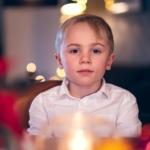En gutt i hvit skjorte ser inn i kamera. Han sitter i en julepyntet stue.