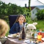 Bilde av ei ung jente som sitter ytterst ved middagsbord i hagen og stirrer tomt ut i luften