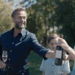 En mann tar i mot en vinflaske. Han ler. I bakgrunnen ser man en ni år gammel gutt.