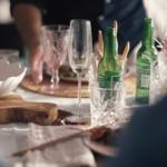 Et detaljbilde fra et middagsbord, med to tomme ølflasker og mange tomme glass.