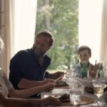En familie sitter rundt et pyntet middagsbord. Det er mange glass og flasker på bordet.