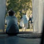 En gutt sitter i døråpningen med ryggen til. Han ser ut på en sommerfest i hagen.