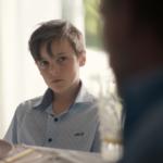 En gutt ser alvorlig inn i kameraet. Han er ca ni år, har brunt hår og er kledd i en brun skjorte.