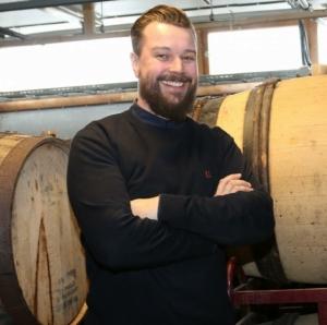 Lervig-sjefen står foran to øl-tønner, iført en svart polotrøye. Han smiler, med armene i kors.