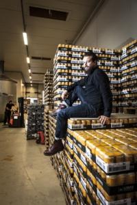 Lervig-sjefen i pent tøy sitter på paller med øl i bryggeriet, og man se en gaffeltruck i bakgrunnen som kjører paller.