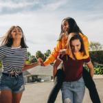 Tre jenter i ungdomsskolealder som er ute å går. Den ene jenta sitter på ryggen til den andre. De ler og koser seg.