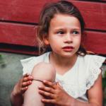 Bilde av ei jente med brunt hår i hestehale og hvit overdel sitter og lener seg mot en rød husvegg. Med barnehagesekken på siden.