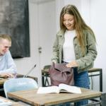 Ung jente som står ved pulten sin og pakker sekken mens hun smiler